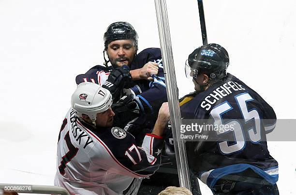 Brandon Dubinsky of the Columbus Blue Jackets mixes it up with Dustin Byfuglien and Mark Scheifele of the Winnipeg Jets during second period action...