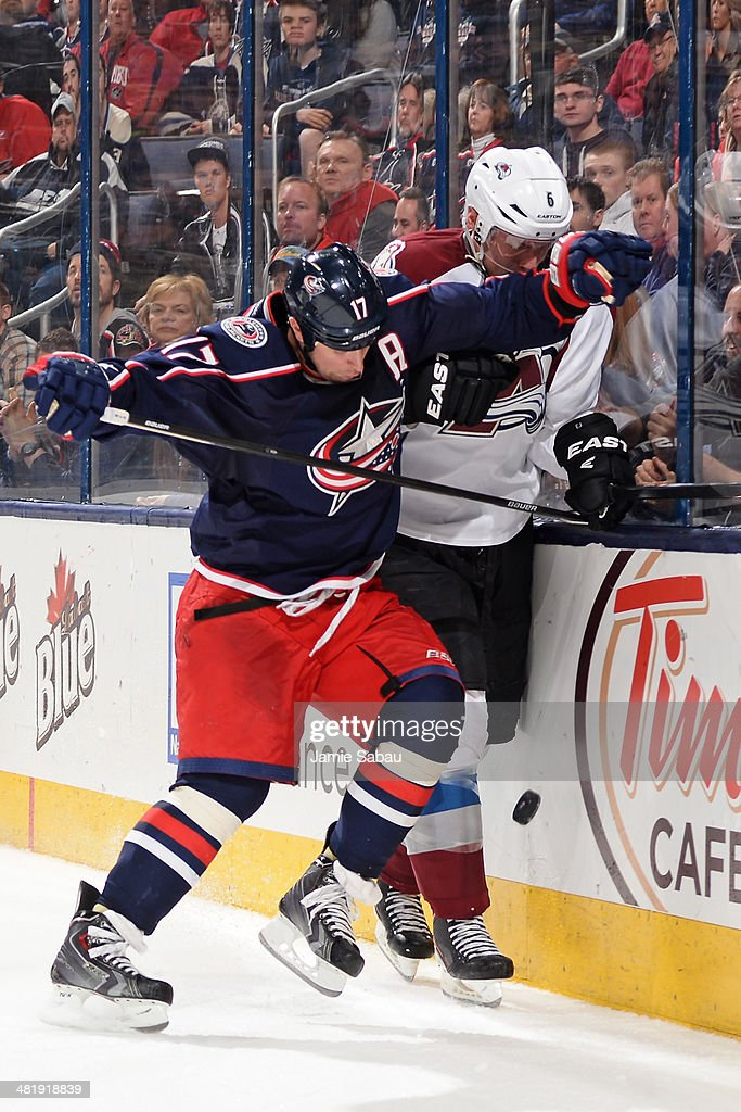 Brandon Dubinsky #17 of the Columbus Blue Jackets pushes Erik Johnson #6 of the Colorado Avalanche against the boards battling for the puck during the third period on April 1, 2014 at Nationwide Arena in Columbus, Ohio. Colorado defeated Columbus 3-2 in overtime.