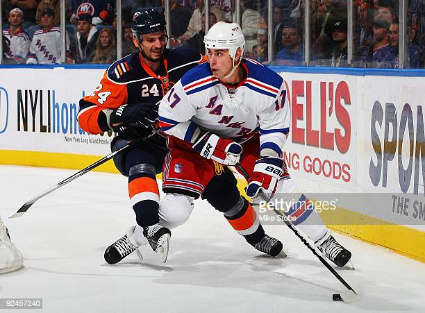 Brandon Dubinsky tries to skate past Radek Martinek of the New York Rangers of the New York Islanders on October 28, 2009 at Nassau Coliseum in...