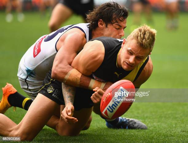 Brandon Ellis of the Tigers handballs whilst being tackled by Brady Grey of the Dockers during the round eight AFL match between the Richmond Tigers...