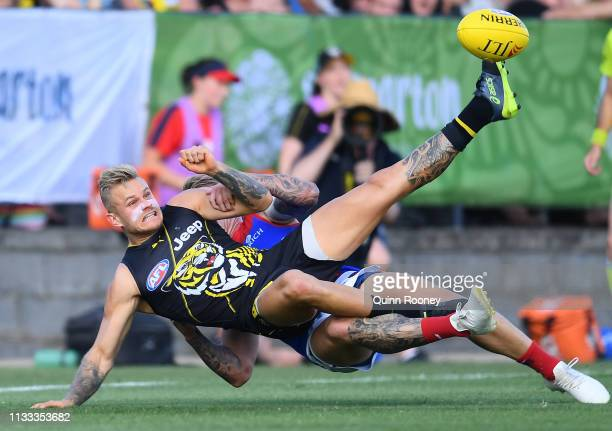 Brandon Ellis of the Tigers handballs whilst being tackled by James Harmes of the Demons during the 2019 JLT Community Series AFL match between the...