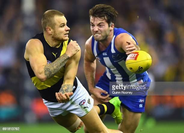 Brandon Ellis of the Tigers handballs whilst being tackled by Luke McDonald of the Kangaroos during the round 11 AFL match between the North...