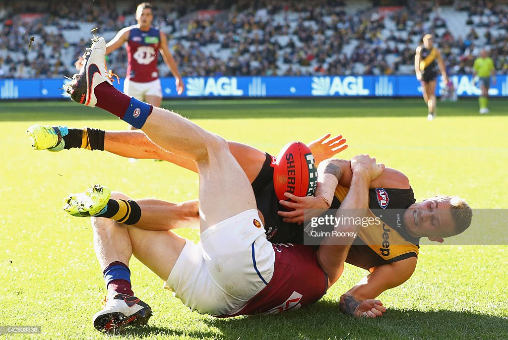 Brandon Ellis of the Tigers is tackled by Daniel Merrett of the Lions during the round 14 AFL match between the Richmond Tigers and the Brisbane Lions at Melbourne Cricket Ground on June 25, 2016 in Melbourne, Australia.