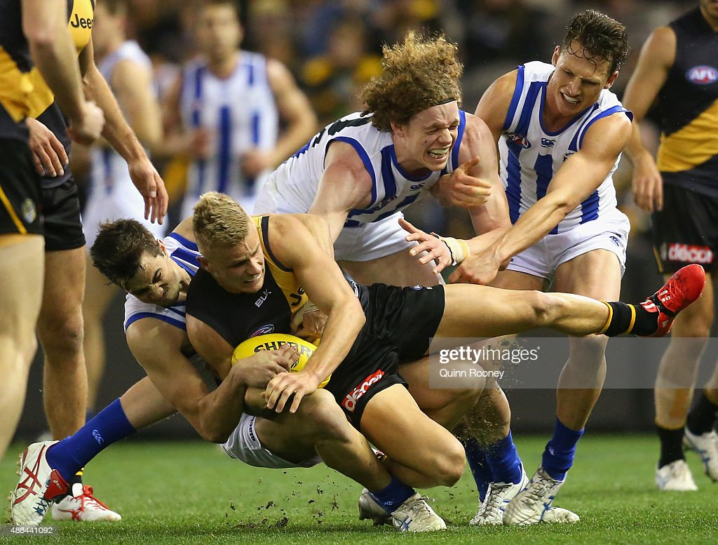 Brandon Ellis of the Tigers is tackled by Taylor Garner of the Kangaroos during the round 23 AFL match between the Richmond Tigers and the North Melbourne Kangaroos at Etihad Stadium on September 4, 2015 in Melbourne, Australia.