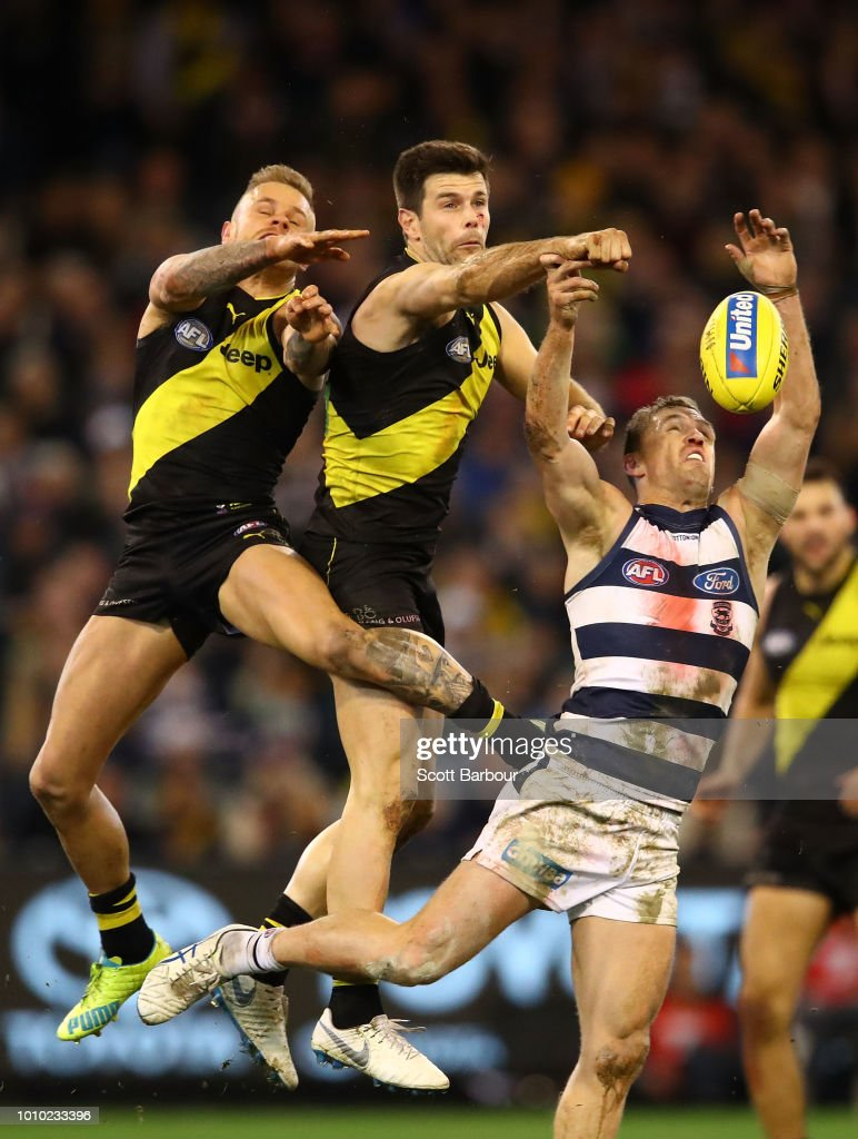 Brandon Ellis of the Tigers, Trent Cotchin of the Tigers and Joel Selwood of the Cats compete for the ball during the round 20 AFL match between the Richmond Tigers and the Geelong Cats at Melbourne Cricket Ground on August 3, 2018 in Melbourne, Australia.