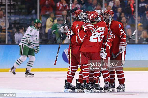 Brandon Fortunato and Robbie Baillargeon congratulate Brandon Hickey of the Boston Terriers after he scored against North Dakota during the first...
