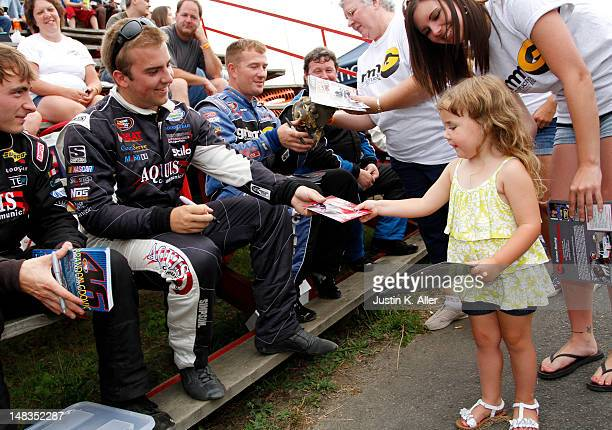 Brandon Gdovic driver of the Aquis Communications/ComServe Toyota sign autographs during the NASCAR KN Pro Series East Samuel 150 on July 14 2012 at...