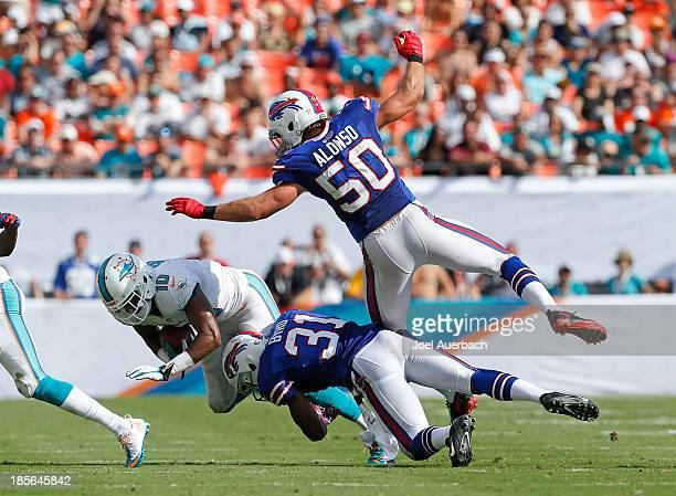 Brandon Gibson of the Miami Dolphins is tackled by Jairus Byrd and Kiko Alonso of the Buffalo Bills on October 20, 2013 at Sun Life Stadium in Miami...
