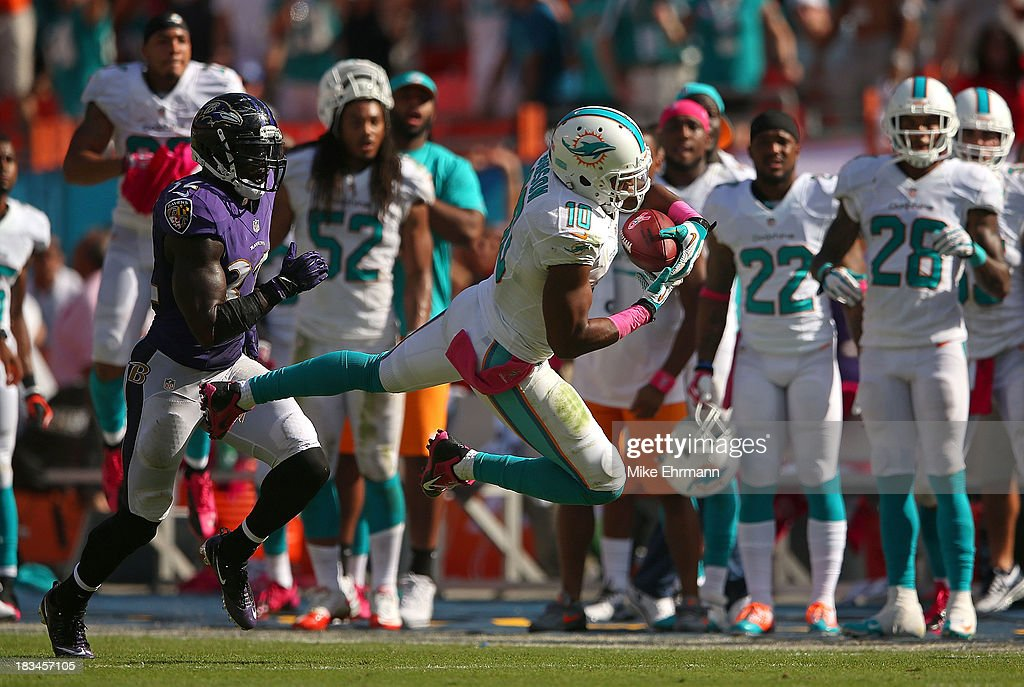 Brandon Gibson #10 of the Miami Dolphins makes a catch over Lardarius Webb #21 of the Baltimore Ravens during a game at Sun Life Stadium on October 6, 2013 in Miami Gardens, Florida.