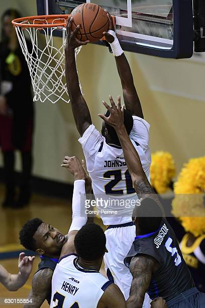 Brandon Goodwin of the Florida Gulf Coast Eagles gets his chin caught on Demetrius Henry of the La Salle Explorers as BJ Johnson of the La Salle...