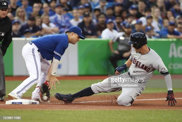 Brandon Guyer of the Cleveland Indians slides safely into third base as Aledmys Diaz of the Toronto Blue Jays cannot get the tag down in time in the...