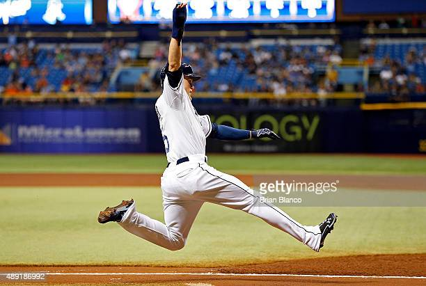 Brandon Guyer of the Tampa Bay Rays leaps to slide home to score off of a double by Richie Shaffer during the first inning of a game against the...