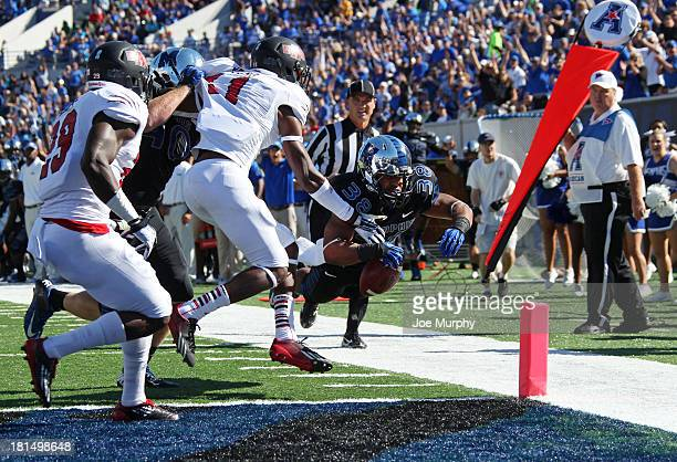 Brandon Hayes of the Memphis Tigers dives over the goal line for a touchdown run against Sterling Young of the Arkansas State Red Wolves on September...