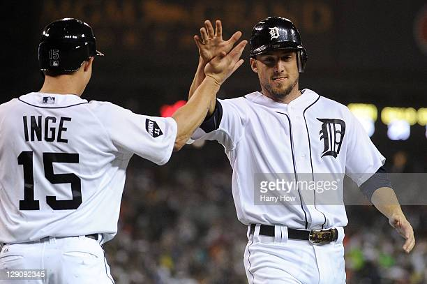 Brandon Inge and Ryan Raburn of the Detroit Tigers celebrate after scoring in the third inning on a double by Miguel Cabrera in Game Four of the...