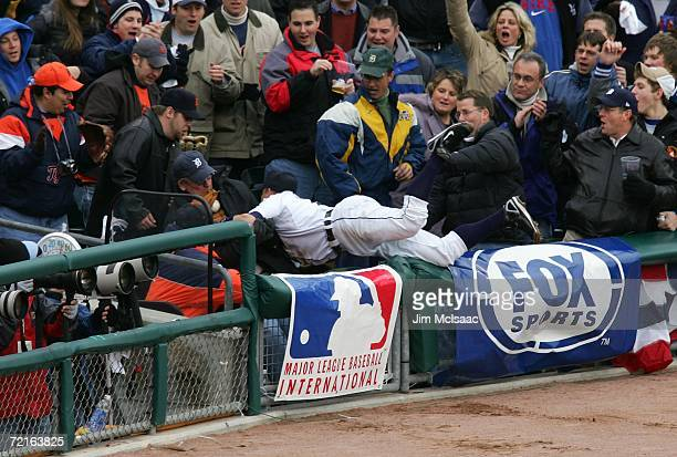 Brandon Inge of the Detroit Tigers falls into the stands as he catches a pop fly in foul territoty hit by Mark Kotsay of the Oakland Athletics during...