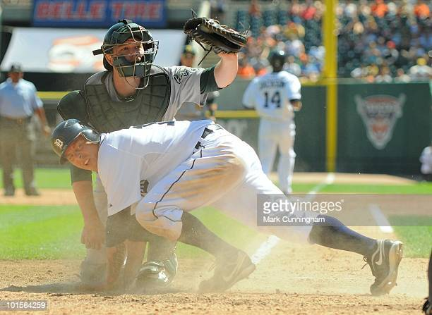 Brandon Inge of the Detroit Tigers is tagged out at home plate by Landon Powell of the Oakland Athletics during the game at Comerica Park on May 30...