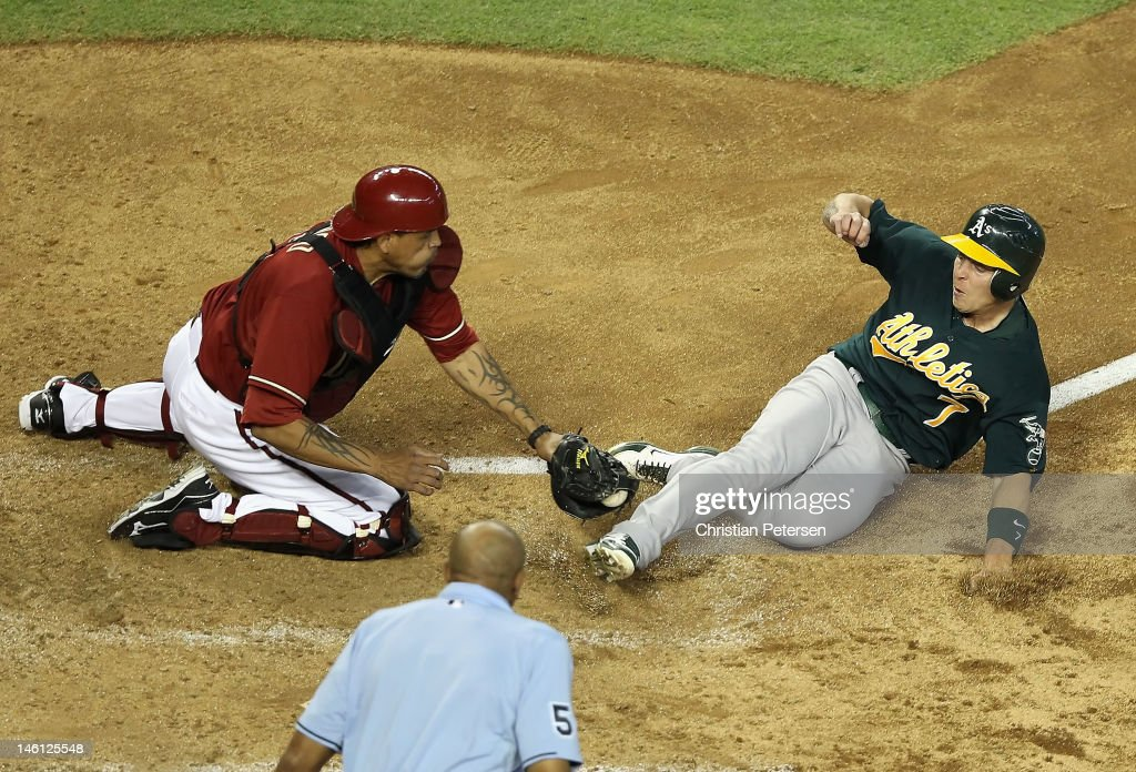 Brandon Inge #7 of the Oakland Athletics safely slides in to score a run past the tag from catcher Henry Blanco #12 of the Arizona Diamondbacks during the fourth inning of the interleague MLB game at Chase Field on June 10, 2012 in Phoenix, Arizona.