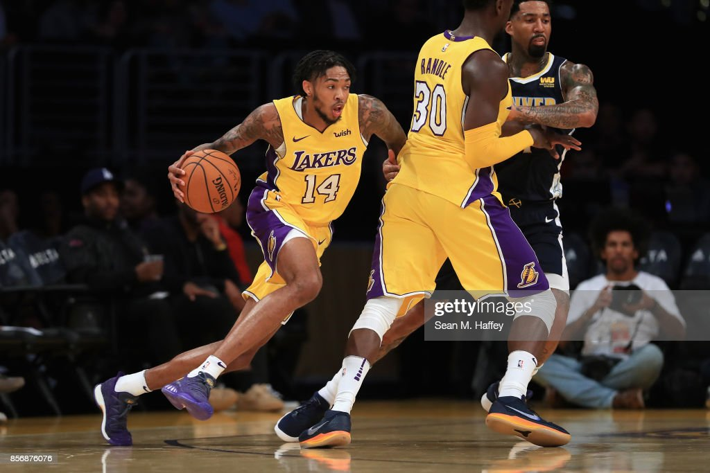 Brandon Ingram #14 dribbles past Julius Randle #30 of the Los Angeles Lakers and Wilson Chandler #21 of the Denver Nuggets during the first half of a preseason game at Staples Center on October 2, 2017 in Los Angeles, California.