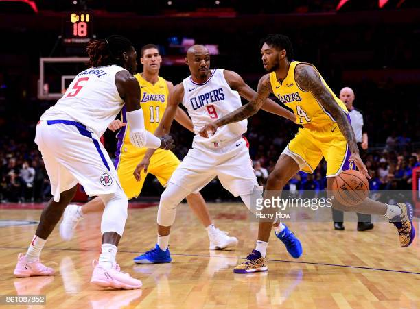 Brandon Ingram of the Los Angeles Lakers attempts a pick and roll with Brook Lopez as he is defenede by CJ Williams and Montrezl Harrell of the LA...