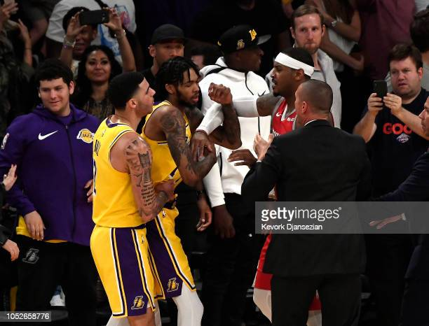 Brandon Ingram of the Los Angeles Lakers is held back by Lonzo Ball as he has words with Carmelo Anthony of the Houston Rockets during the second...