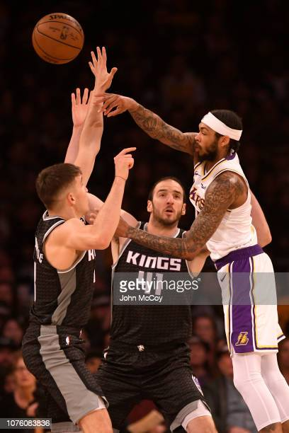 Brandon Ingram of the Los Angeles Lakers passes the ball over Bogdan Bogdanovic and Kosta Koufos of the Sacramento Kings in the first half at Staples...