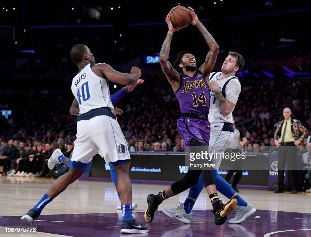 Brandon Ingram of the Los Angeles Lakers reacts as he is fouled while driving the lane between Luka Doncic and Dorian FinneySmith of the Dallas...