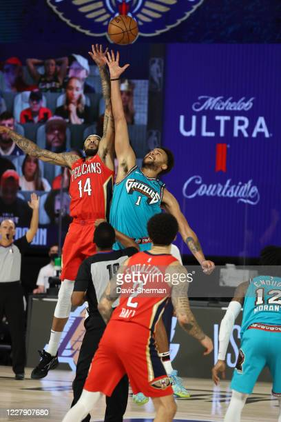 Brandon Ingram of the New Orleans Pelicans and Kyle Anderson of the Memphis Grizzlies reach for the ball during the game on August 3 2020 at HP Field...
