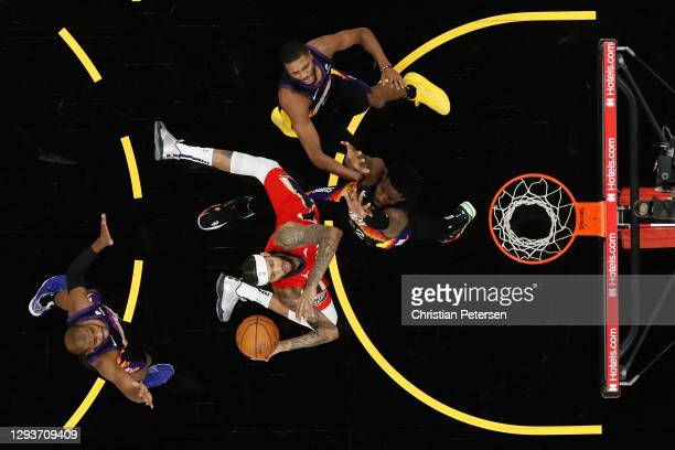 Brandon Ingram of the New Orleans Pelicans attempts a shot defended by Deandre Ayton, Mikal Bridges and Chris Paul of the Phoenix Suns during the...
