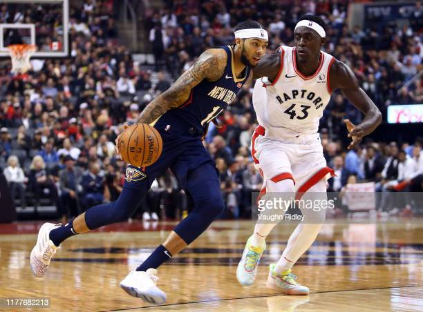 Brandon Ingram of the New Orleans Pelicans dribbles the ball as Pascal Siakam of the Toronto Raptors defends during the first half of an NBA game at...