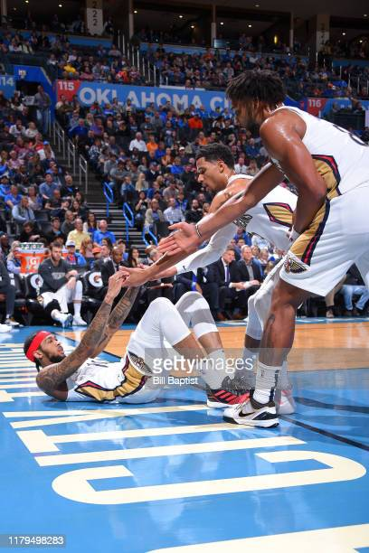 Brandon Ingram of the New Orleans Pelicans is helped up by teammates Josh Hart and Jahlil Okafor during a game against the Oklahoma City Thunder on...
