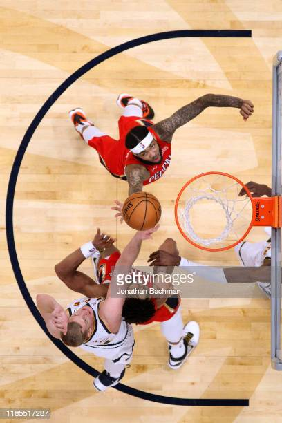 Brandon Ingram of the New Orleans Pelicans Jahlil Okafor and Mason Plumlee of the Denver Nuggets go for rebound during a game at the Smoothie King...