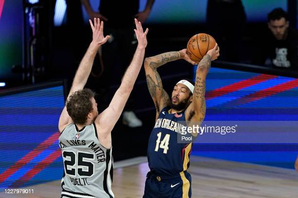 Brandon Ingram of the New Orleans Pelicans passes the ball over Jakob Poeltl of the San Antonio Spurs during the first half at HP Field House at ESPN...