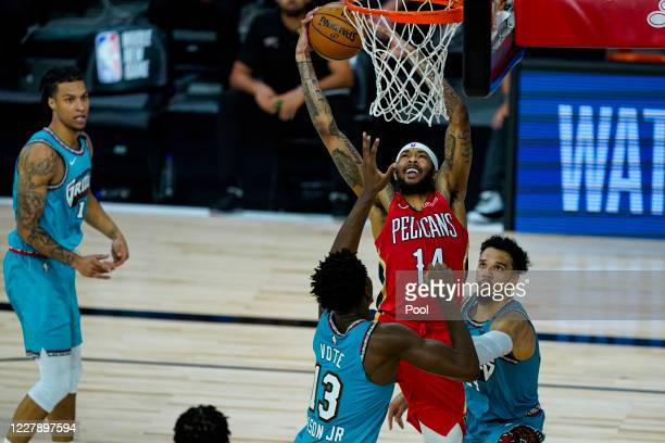Brandon Ingram of the New Orleans Pelicans shoots between Jaren Jackson Jr #13 and Dillon Brooks of the Memphis Grizzlies during the second half of...