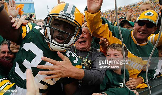 Brandon Jackson of the Green Bay Packers celebrates a touchdown with a Lambeau Leap into the stands against of the Buffalo Bills at Lambeau Field on...