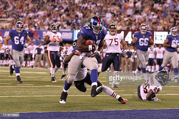 Brandon Jacobs of the New York Giants breaks the tackle of Chris Harris of the Chicago Bears and scores a touchdown during their pre season game on...