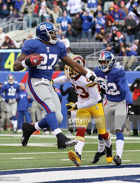 Brandon Jacobs of the New York Giants carries the ball past DeAngelo Hall of the Washington Redskins into the endzone for a first quarter touchdown...