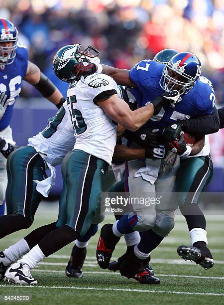 Brandon Jacobs of the New York Giants runs against Stewart Bradley of the Philadelphia Eagles during the NFC Divisional Playoff Game on January 11...