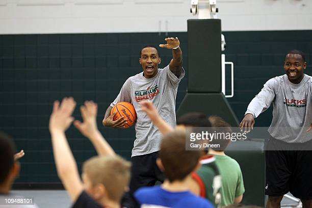 Brandon Jennings of the Milwaukee Bucks and assistant coach Anthony Goldwire work with participants during the YMCA basketball clinic on February 27,...