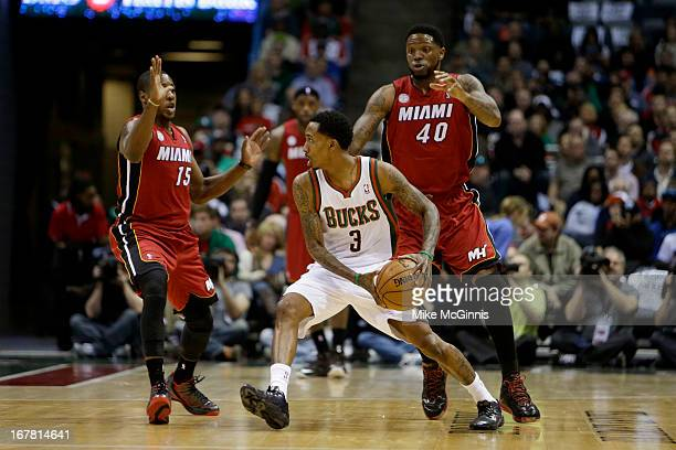 Brandon Jennings of the Milwaukee Bucks gets double teamed by Mario Chalmers and Undonis Haslem of the Miami Heat during Game Three of the Western...
