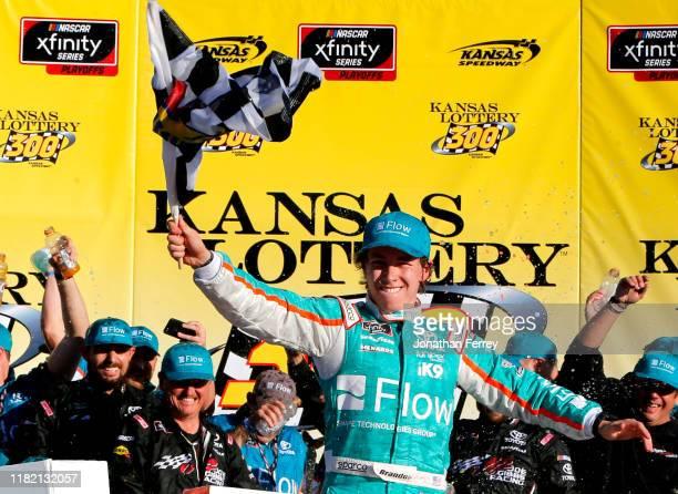 Brandon Jones, driver of the Flow Toyota, celebrates in victory lane after winning the NASCAR Xfinity Series Kansas Lottery 300 at Kansas Speedway on...