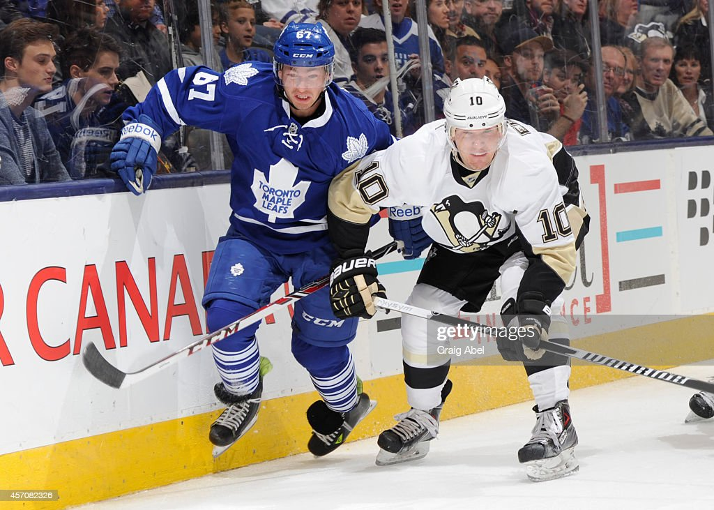 Brandon Kozun #67 of the Toronto Maple Leafs battles for the puck with Christian Ehrhoff #10 of the Pittsburgh Penguins during NHL game action October 11, 2014 at the Air Canada Centre in Toronto, Ontario, Canada.