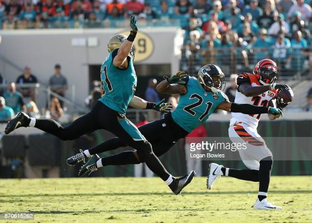 Brandon LaFell of the Cincinnati Bengals reaches for the football in front of Paul Posluszny and AJ Bouye of the Jacksonville Jaguars in the second...