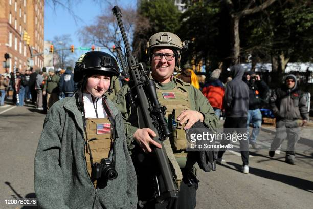 Brandon Lewis of Bergen New York carries a 50caliber Barrett M82A1 rifle through the streets following a rally organized by The Virginia Citizens...