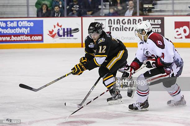 Brandon Lindberg of the Sarnia Sting tries to beat Graham Knott of the Niagara IceDogs to a loose puck during a game at the Meridian Center on...