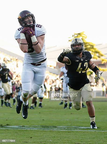 Brandon Lingen of the Minnesota Golden Gophers make a catch in the end zone for a touchdown as Andy James Garcia of the Purdue Boilermakers trails at...