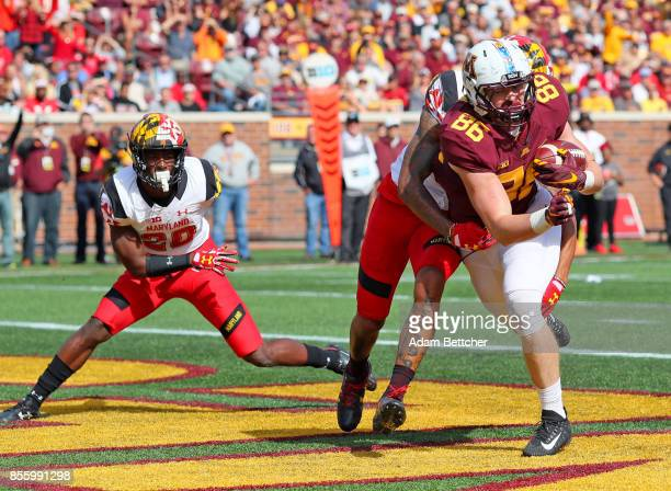 Brandon Lingen of the Minnesota Golden Gophers pulls in a touchdown while being tackled by Josh Woods of the Maryland Terrapins in the third quarter...