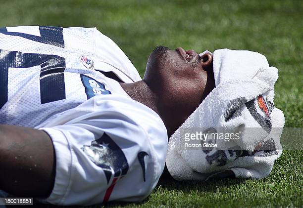 Brandon Lloyd covers his face with a towel as he stretches on the sidelines as the New England Patriots held practice with the New Orleans Saints at...