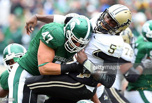 Brandon Long of the Michigan State Spartans takes down Justin Siller of the Purdue Boilermakers at Spartan Stadium on November 8, 2008 in East...