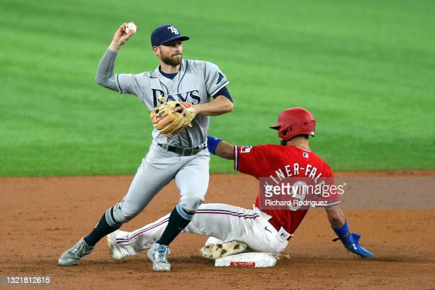 Brandon Lowe of the Tampa Bay Rays tries to make the throw to first as Isiah Kiner-Falefa of the Texas Rangers slides into second in the third inning...