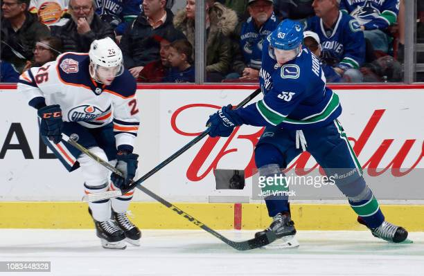 Brandon Manning of the Edmonton Oilers checks Bo Horvat of the Vancouver Canucks during their NHL game at Rogers Arena January 16 2019 in Vancouver...